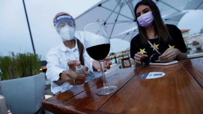 Una cliente con mascarilla por el coronavirus desinfecta una copa de vino en un restaurante en Panamá.