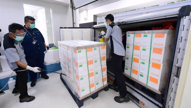 Técnicos desinfectan un lote del primer cargamento de vacunas contra la COVID-19 de la empresa china Sinovac llegado a Indonesia, en el aeropuerto de Bandung.