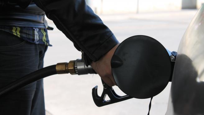 Un trabajador sirve gasolina a un vehículo.