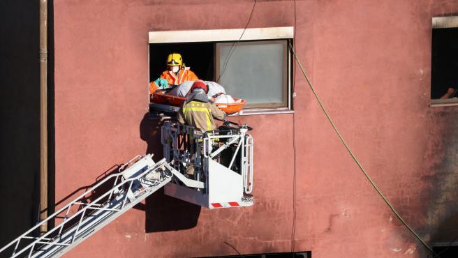 Los bomberos extraen una de las víctimas mortales del incendio de Badalona.