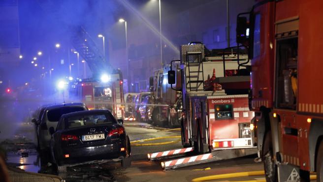 Una veintena de dotaciones de los Bomberos de la Generalitat trabajan esta noche en la extinción del incendio de una nave abandonada en la localidad barcelonesa de Badalona
