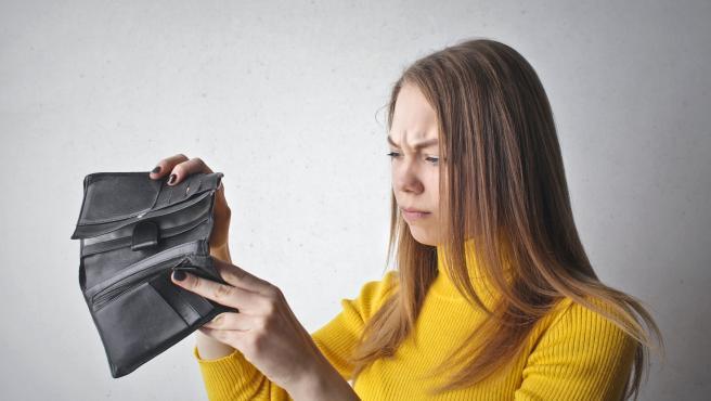 Una joven observa su cartera vacía.