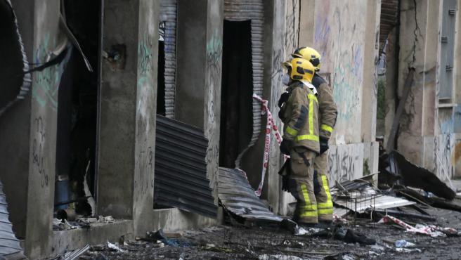Dos bomberos observan el interior de la nave incendiada en Badalona, en una inspección este viernes 11 de diciembre de 2020.