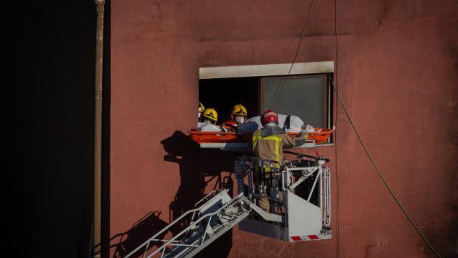 Bomberos retiran el cadáver de una de las personas fallecidas en el incendio de ayer en la nave okupada del barrio de Gorg, en Badalona, Barcelona, Catalunya (España), a 10 de diciembre de 2020.