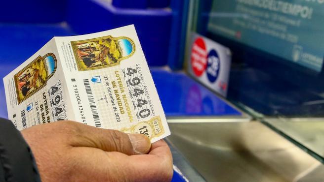 Una persona compra un décimo para el Sorteo Extraordinario de la Lotería de Navidad 2020.