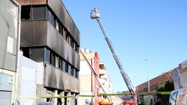 Una grúa de los Bombers supervisa este domingo los trabajos de derribo de la nave incendiada en Badalona.