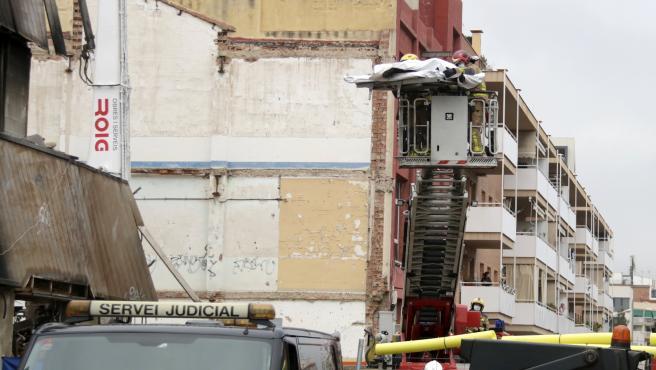 Los bomberos retiran el cuerpo de la cuarta víctima mortal del incendio de la nave de Badalona.