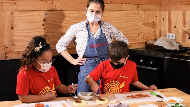 La chef Ada Parellada elabora una receta de mini pizzas saludables con la ayuda de dos niños.