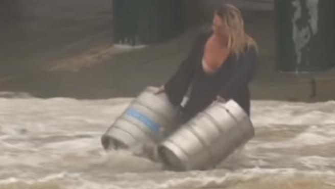 Una mujer se lanza a la calle inundada para agarrar dos barriles de cerveza.