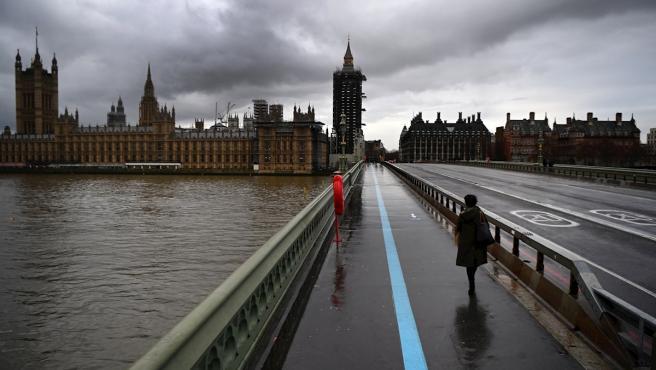 Un viandante camina sobre el puente de Westminster en Londres, Reino Unido.