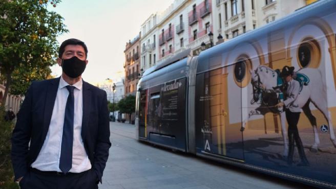 Juan Marín junto al tranvía de Sevilla con publicidad de Jerez