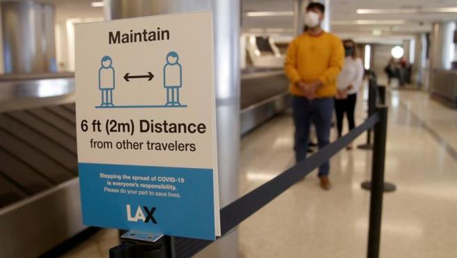 Pasajeros esperan para realizarse la prueba de COVID-19, antes de embarcar en sus vuelos en el Aeropuerto Internacional de Los Ángeles (California, EE UU).