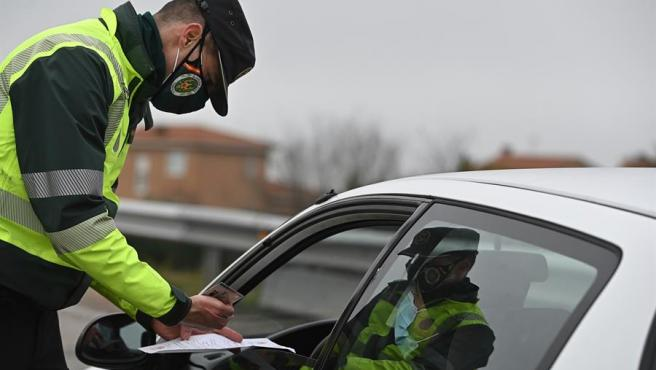 Un guardia civil solicita la documentación a un conductor en un control montado en la A-5