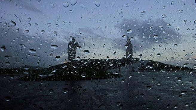 La Torre de Hércules y la estatua de Breogán vistas tras un cristal salpicado de gotas de lluvia este lunes en el que la borrasca Bella seguirá aportando inestabilidad con todo el litoral gallego en alerta y nivel rojo en A Coruña.