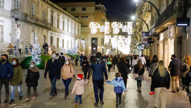 Transeúntes pasean bajo las luces navideñas, llevando mascarilla, alguno con gorro navideño, en Vigo, Galicia (España), a 25 de diciembre de 2020