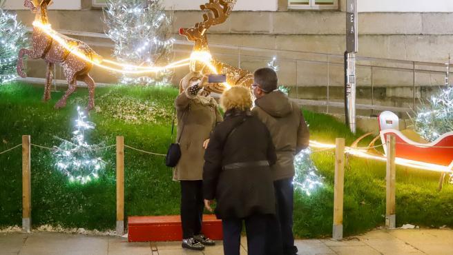 Transeúntes se hacen fotos bajo las luces navideñas, en Vigo, Galicia (España), a 25 de diciembre de 2020. Vigo está cerrada perimetralmente, pero abierta entre el 23 y 25 de diciembre para permitir encuentros familiares.