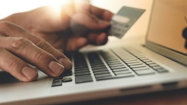 Persona usando un ordenador con tarjeta de crédito y haciendo compras online.