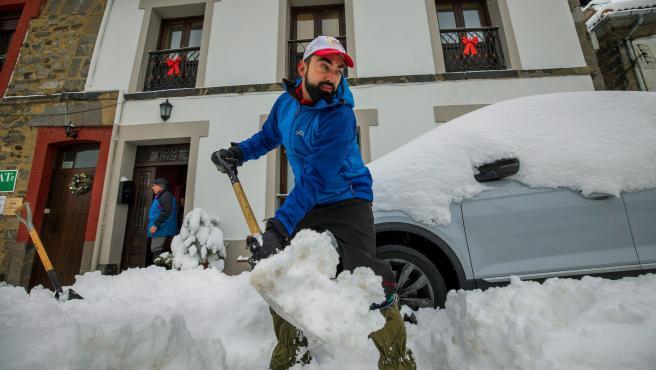 Un hombre retira nieve delante de su casa en Pajares, Asturias.