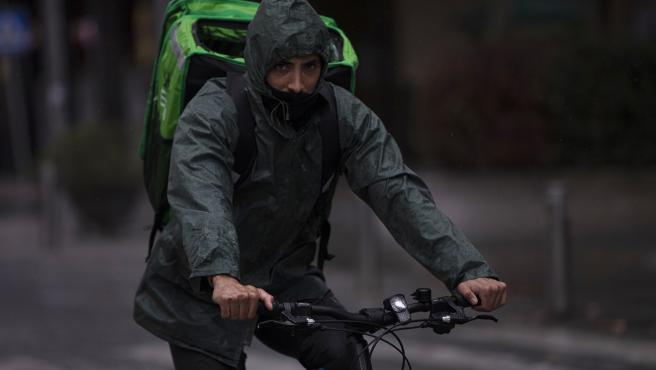 Un rider (repartidor) trabaja bajo la lluvia protegido con un impermeable