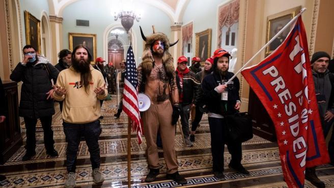 Varios asaltantes al congreso llegan a las puertas de la cámara ataviados con atuendos de nativos americanos.