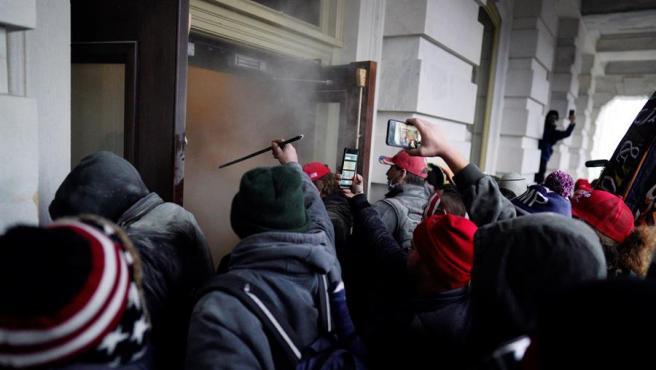 Seguidores de Donald Trump son repelidos con gas lacrimógeno mientras intentan entrar en el Capotolio.