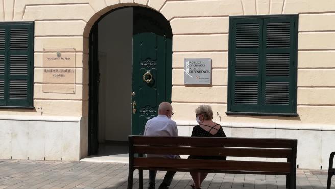 Dos personas mayores conversan sentadas en un banco y con mascarilla, ante la Residencia Geriátrica Asistida del Ayuntamiento de Mahón en la Calle Cós de Gràcia.
