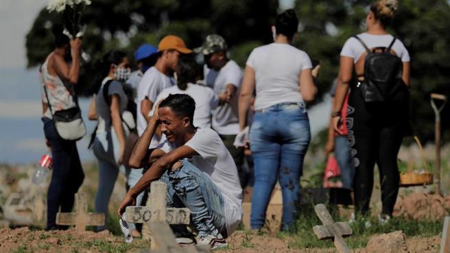 Un hombre llora la muerte de un familiar fallecido por COVID-19, durante el entierro en un cementerio de Río de Janeiro, Brasil.