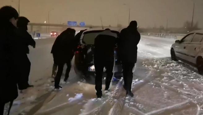 Varios jugadores del Rayo Vallecano ayudan a un coche a poder continuar su marcha.