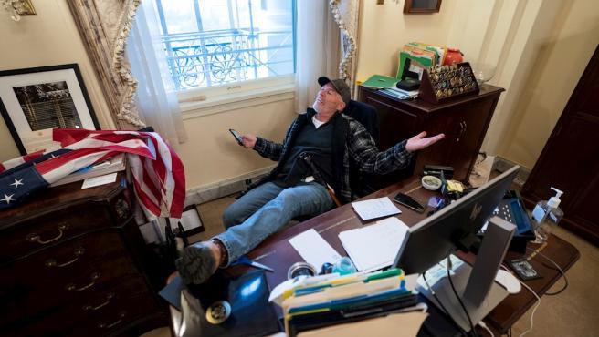 Richard Barnett, un seguidor de Donald Trump, se sienta en el escritorio de la presidenta de la Cámara de Representantes de Estados Unidos, Nancy Pelosi, tras irrumpir en el Capitolio de EE UU.