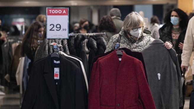una mujer ojea una prenda en una tienda de ropa durante el comienzo de las rebajas de invierno.