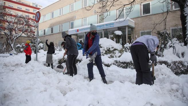 Varios voluntarios despejan con palas el acceso a una de las entradas del Hospital Gregorio Marañón de Madrid.