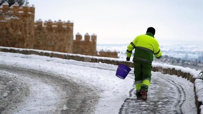 Un trabajador echando sal en una zona nevada.