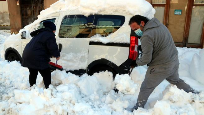 Unos vecinos intentando desenterrar su coche en Falset.