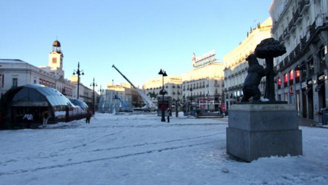 La nieve congelada cubre el suelo de la Puerta del Sol de Madrid, junto a la estatua de 'El oso y el madroño'.