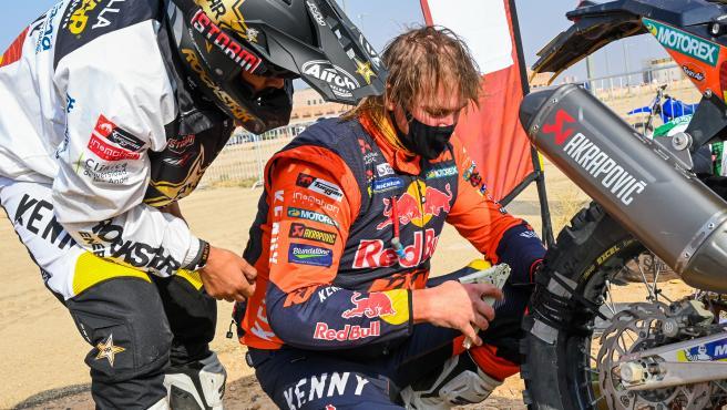 Toby Price (d) arregla su moto en el vivac del Dakar con bridas y cinta americana