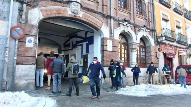 Los vecinos recogen sal para poder deshelar la nieve que se ha congelado en las calles de Madrid.
