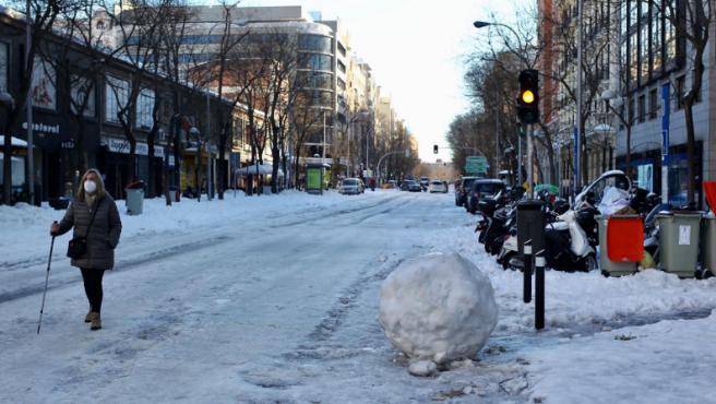 Una mujer camina por la calzada junto a una peligrosa bola de nieve helada, en la calle Ortega y Gasset de Madrid.