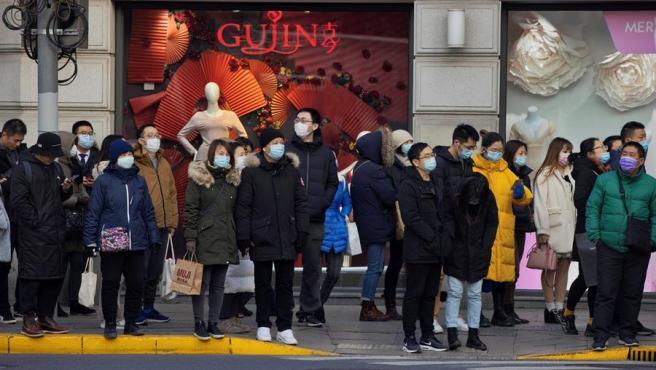 Ciudadanos con mascarillas por el coronavirus, en un paso de cebra en Shanghái, China.