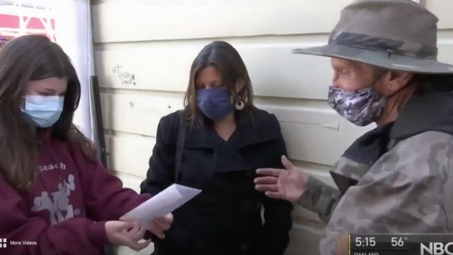 La joven entregando la recaudación al sintecho.NBC