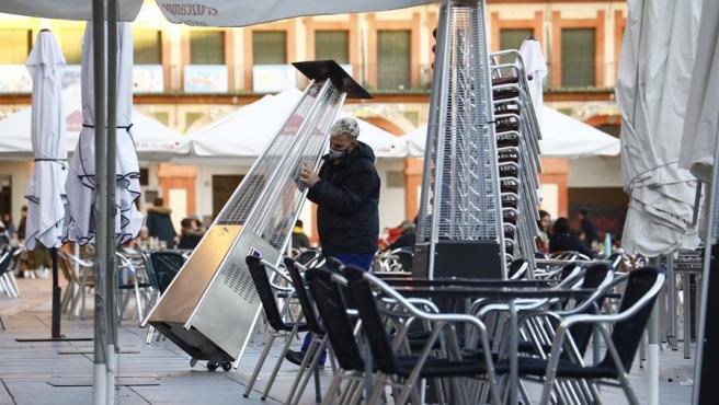Un trabajador recoge el mobiliario de la terraza de un restaurante en el centro de Córdoba.