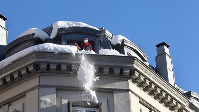 Un operario retira la nieve de una terraza de un edificio en Madrid.