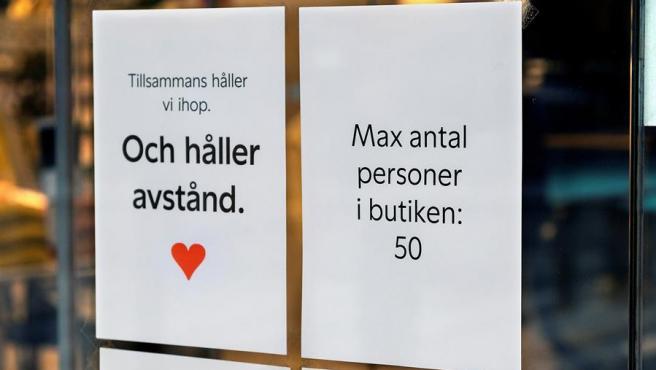 Dos carteles que dicen 'Mantener la distancia' y 'Número máximo de personas en la tienda 50' en una tienda en Estocolmo