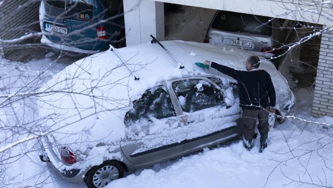 Un hombre retira la nieve que hay sobre su coche tras el paso de la nevada fruto del temporal Filomena por la Comunidad de Madrid.