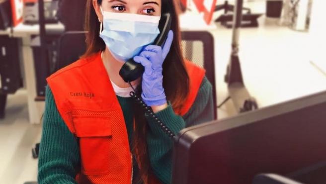 Una voluntaria de Cruz Roja atiende el teléfono durante la pandemia