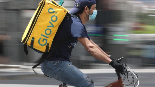 Un repartidor de Glovo monta una bicicleta durante su jornada laboral