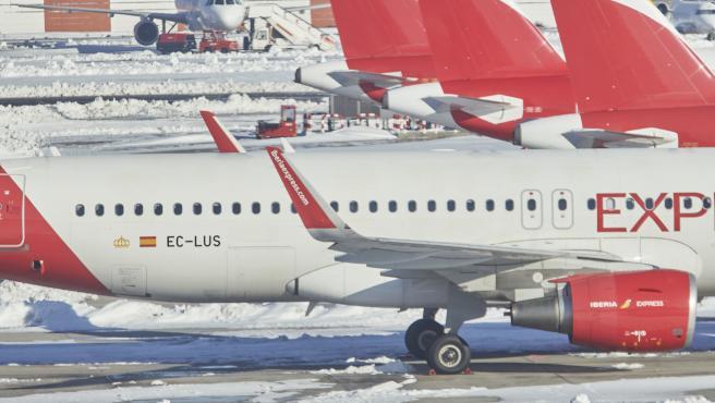 Una excavadora trabaja para retirar la nieve y el hielo de la pista del aeropuerto Madrid-Barajas Adolfo Suárez.