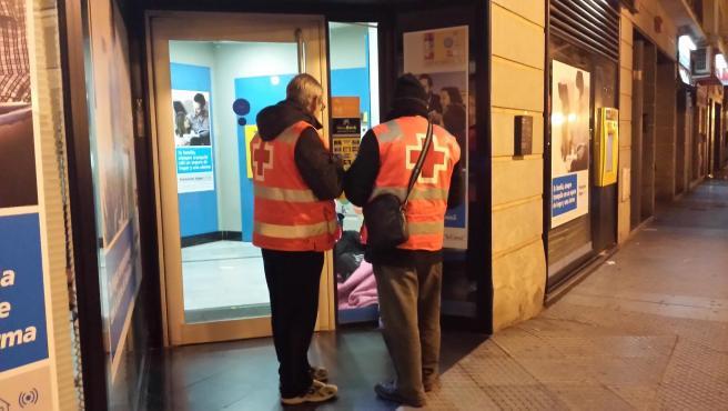 Voluntarios de Cruz Roja ayudan a una persona sin hogar.