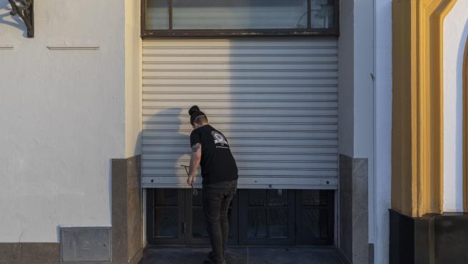 Un hostelero echa la persiana de su establecimiento