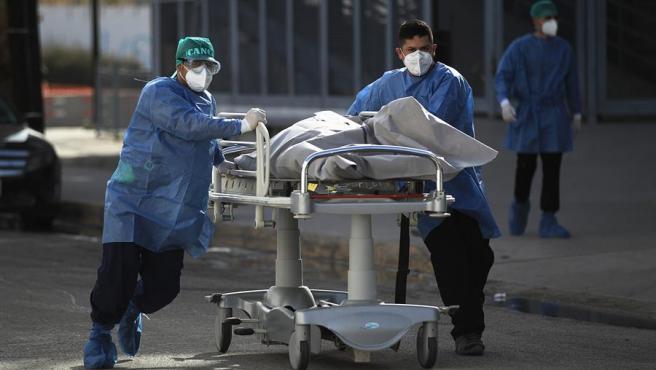 Trabajadores sanitarios trasladan el cuerpo de una persona fallecida por COVID-19 en un hospital de Ciudad Juárez, México.