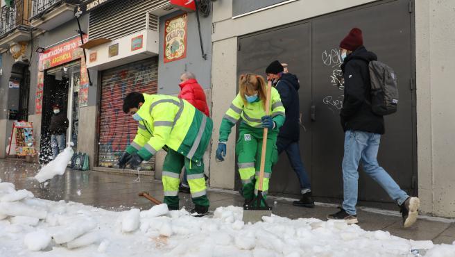 Dos operarias de limpieza trabajan en la retirada de la nieve y el hielo de la calle Argumosa ubicada en Lavapiés tras la gran nevada provocada por la borrasca 'Filomena', en Madrid, (España), a 15 de enero de 2021.